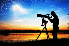 Silueta del hombre joven que mira a través de un telescopio imagen de archivo