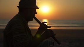 Silueta del hombre mayor que toca la flauta de bambú en la playa en la puesta del sol almacen de metraje de vídeo