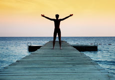 Silueta del hombre pacífico libre en la puesta del sol foto de archivo