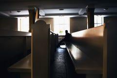 Silueta del hombre pecador que ruega en el asiento de la iglesia en los bancos Fotos de archivo libres de regalías