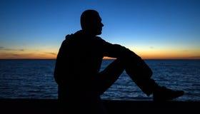 Silueta del hombre pensativo tranquilo que mira la puesta del sol Fotos de archivo