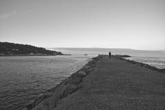 Silueta del hombre que camina en el rompeolas en puesta del sol por Océano Atlántico Fotografía de archivo libre de regalías