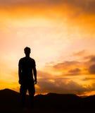 Silueta del hombre que coloca un solitario encima de la montaña con crepúsculo anaranjado Foto de archivo libre de regalías