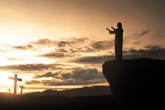 Silueta del hombre que hace frente a la cruz y que ruega Imagen de archivo