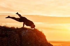 Silueta del hombre que hace la meditación de la yoga contra el cielo hermoso con las nubes Foto de archivo libre de regalías