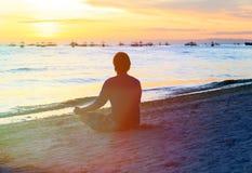 Silueta del hombre que medita en la playa de la puesta del sol Foto de archivo libre de regalías