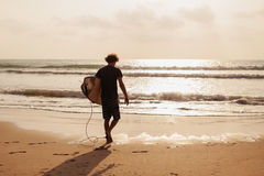 Silueta del hombre que practica surf en la playa Foto de archivo