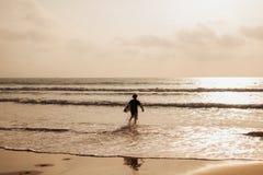Silueta del hombre que practica surf en ondas Foto de archivo libre de regalías