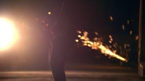 Silueta del hombre que realiza elementos marciales a través de las chispas de la amoladora en la noche - voltereta trasera, a cám almacen de video