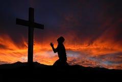 Silueta del hombre que ruega a una cruz con el cloudscape divino su Imagen de archivo libre de regalías