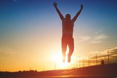 Silueta del hombre que salta en fondo de la puesta del sol Fotos de archivo libres de regalías