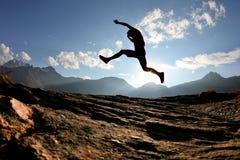 Silueta del hombre que salta en las montan@as suizas Foto de archivo