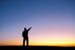 Silueta del hombre que señala el dedo en aire en la puesta del sol Imágenes de archivo libres de regalías