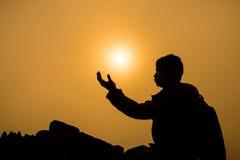 Silueta del hombre que se arrodilla y que ruega sobre fondo hermoso de la salida del sol Imágenes de archivo libres de regalías