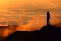 Silueta del hombre que se coloca en el top de la montaña Foto de archivo