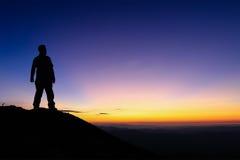 Silueta del hombre que se coloca en el top de la montaña para gozar de colou imágenes de archivo libres de regalías