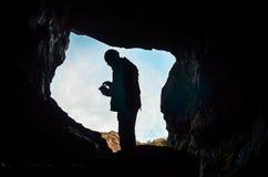 Silueta del hombre que se coloca en una cueva oscura Imágenes de archivo libres de regalías