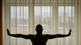 Silueta del hombre que se coloca y que estira delante de ciudad de la mañana de la ventana de las cortinas del amarillo anaranjad almacen de video