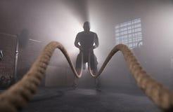 Silueta del hombre que se resuelve con las cuerdas de la batalla en el gimnasio fotografía de archivo