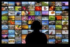 Silueta del hombre que se sienta delante de las pantallas de observación de las multimedias de la pared video fotos de archivo libres de regalías