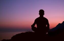 Silueta del hombre que se sienta en actitud de la meditación Foto de archivo
