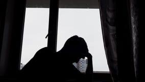 Silueta del hombre triste desesperado en la oscuridad delante de una ventana metrajes