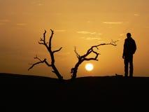 Silueta del hombre y de la puesta del sol imagenes de archivo