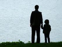 Silueta del hombre y del niño en la tarde Fotografía de archivo libre de regalías