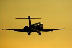 Silueta del jet alrededor a aterrizar en el sol de configuración. Imagen de archivo