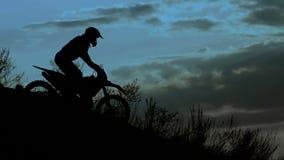 Silueta del jinete en la noche Él va abajo de la colina en su bici extrema del motocrós almacen de metraje de vídeo