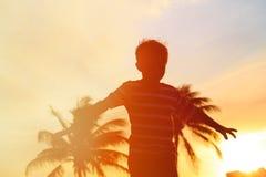Silueta del juego del niño pequeño en la playa de la puesta del sol Imagen de archivo libre de regalías