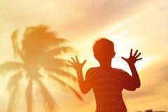 Silueta del juego del niño pequeño en la playa de la puesta del sol Fotos de archivo libres de regalías