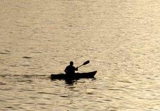 Silueta del kayaer indefinido en el agua en el tiempo hermoso de la puesta del sol Santa Cruz foto de archivo