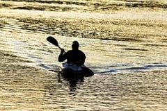 Silueta del kayaker en la puesta del sol Fotografía de archivo