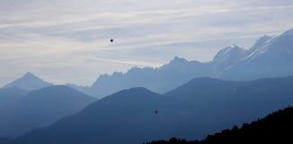 Silueta del macizo de Mont Blanc con los globos del aire caliente en cielo imágenes de archivo libres de regalías