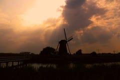 Silueta del molino de viento bajo puesta del sol imagen de archivo
