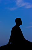 Silueta del monje meditating Imagenes de archivo