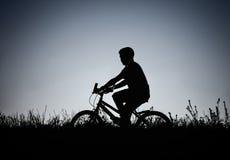 Silueta del montar a caballo del muchacho en la bicicleta en el campo Fotos de archivo libres de regalías