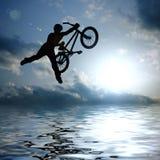 Silueta del muchacho de salto con la bicicleta Fotos de archivo