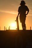 Silueta del muchacho del adolescente con el tablero del patín en la puesta del sol Fotos de archivo libres de regalías