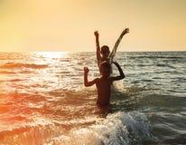 Silueta del muchacho dos que salta en el mar Fotos de archivo libres de regalías
