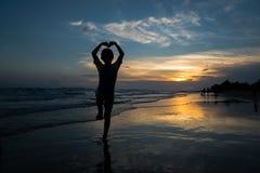 Silueta del muchacho joven que hace la muestra del corazón con sus brazos en el b foto de archivo libre de regalías