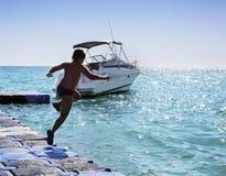 Silueta del muchacho que salta en el mar Imagen de archivo libre de regalías