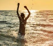 Silueta del muchacho que salta en el mar Foto de archivo