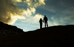Silueta del muchacho y de la muchacha en puesta del sol fotos de archivo