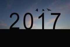Silueta del número 2017 en el tejado y la puesta del sol de la casa en twilig Foto de archivo libre de regalías