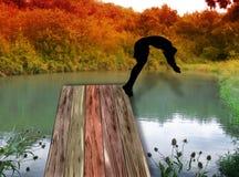 Silueta del nadador que salta de un embarcadero de madera en el lago Imágenes de archivo libres de regalías