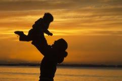 Silueta del niño de elevación de la madre durante puesta del sol Imágenes de archivo libres de regalías