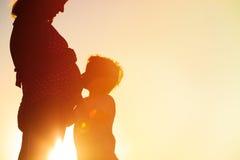 Silueta del niño pequeño que abraza la panza embarazada de la madre en la playa Fotografía de archivo