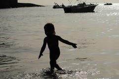 Silueta del niño en el mar Fotos de archivo libres de regalías